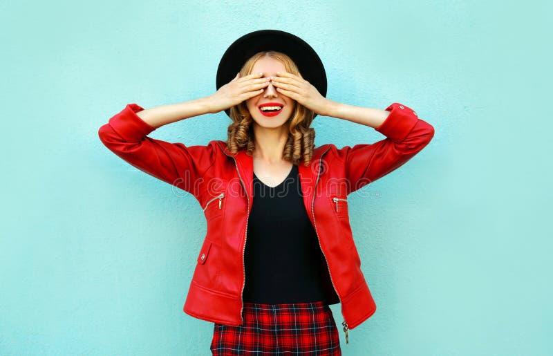 愉快的微笑的妇女闭上她的眼睛用她的手,做愿望,佩带的红色夹克,在蓝色墙壁上的黑帽会议 库存图片