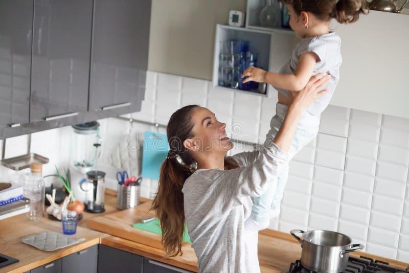 愉快的微笑的妈咪藏品女儿在厨房里 免版税库存照片
