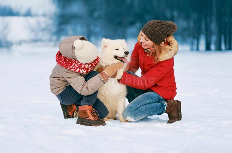 愉快的微笑的家庭获得乐趣一起在走与白色萨莫耶特人狗的冬日、母亲和孩子 免版税库存图片
