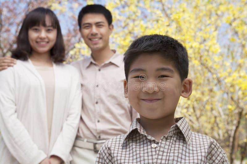 愉快的微笑的家庭画象在公园春天,北京,中国 免版税库存照片