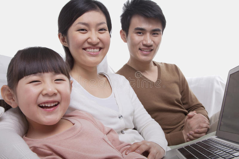 愉快的微笑的家庭画象坐沙发使用膝上型计算机,看照相机,演播室射击 免版税库存图片