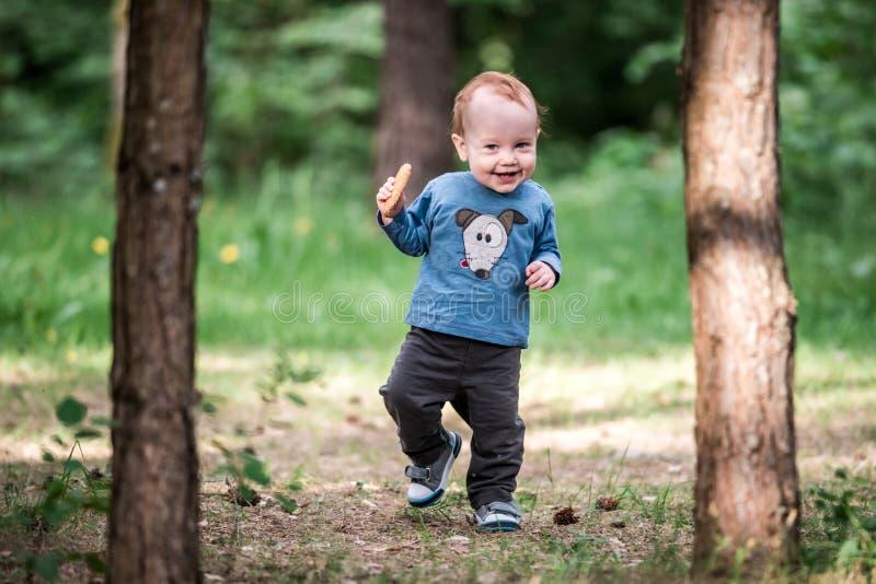 愉快的微笑的小孩在森林里 图库摄影