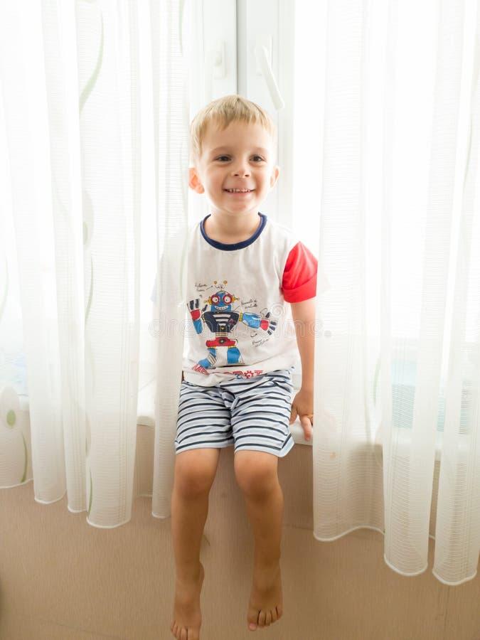 愉快的微笑的小孩男孩画象在家坐窗台在明亮的好日子 图库摄影