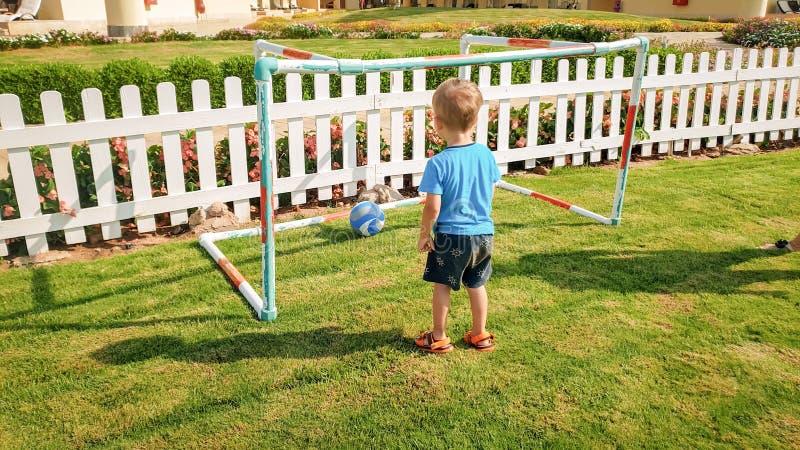 愉快的微笑的小孩男孩计分的目标的图象在橄榄球场的在公园 活跃儿童做体育 图库摄影