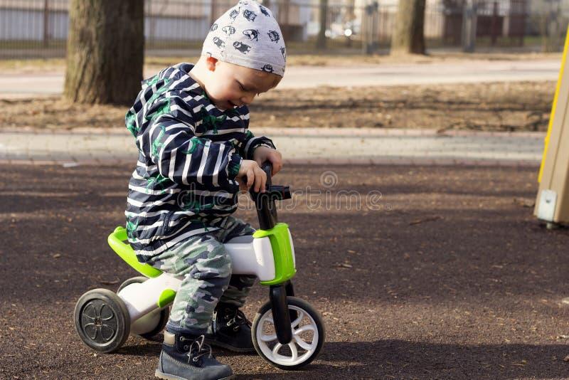 愉快的微笑的小孩男孩骑马自行车 享受自行车乘驾的孩子 活跃小孩 概念查出的体育运动白色 教育玩具为 库存照片