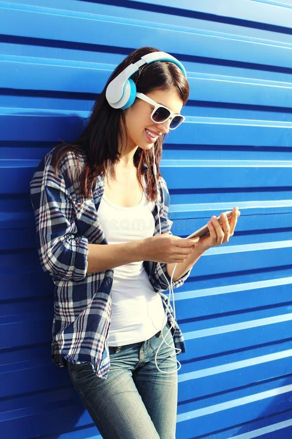 愉快的微笑的少妇听到在耳机的音乐和使用智能手机 免版税库存图片