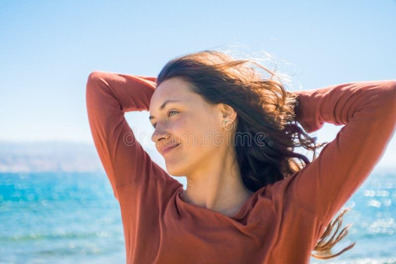 愉快的微笑的少妇画象海滩和海背景的 与女孩长的头发的风戏剧 免版税库存图片