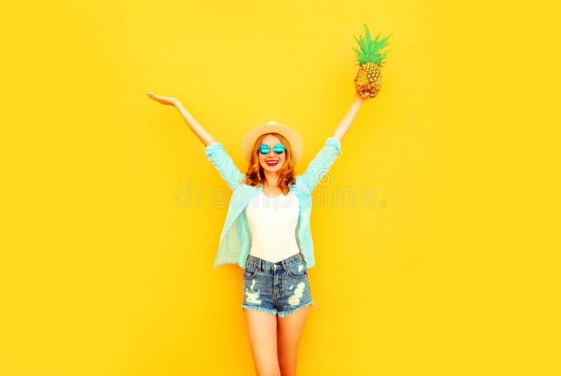愉快的微笑的年轻女人举她的手用菠萝获得乐趣在夏天草帽,太阳镜,在五颜六色的黄色的短裤 图库摄影