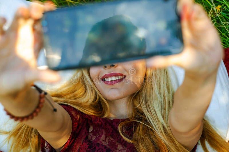 愉快的微笑的年轻女人做selfie和在秋天季节的享用自然 库存图片