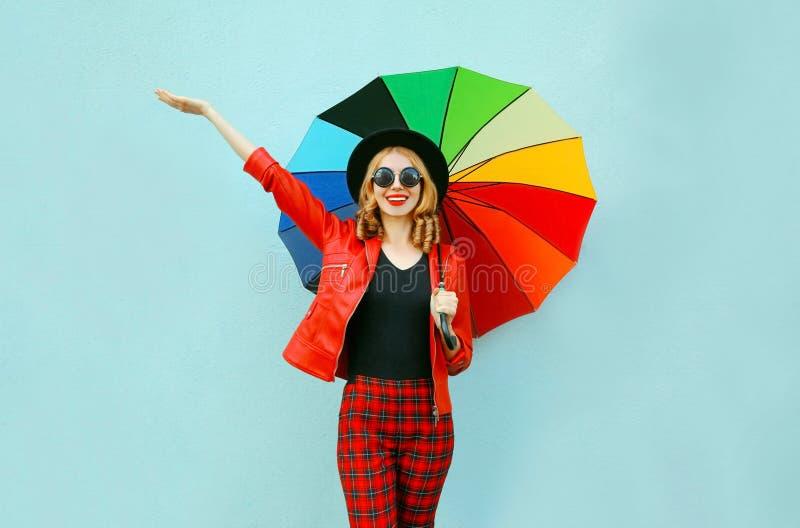 愉快的微笑的年轻女人在手上的拿着五颜六色的伞,佩带的红色夹克,在蓝色墙壁上的黑帽会议 免版税库存照片