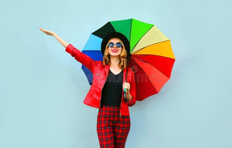 愉快的微笑的年轻女人在手上的拿着五颜六色的伞,佩带的红色夹克,在蓝色墙壁上的黑帽会议 免版税库存图片