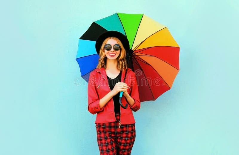 愉快的微笑的年轻女人在手上的拿着五颜六色的伞,佩带的红色夹克,在蓝色墙壁上的黑帽会议 免版税图库摄影