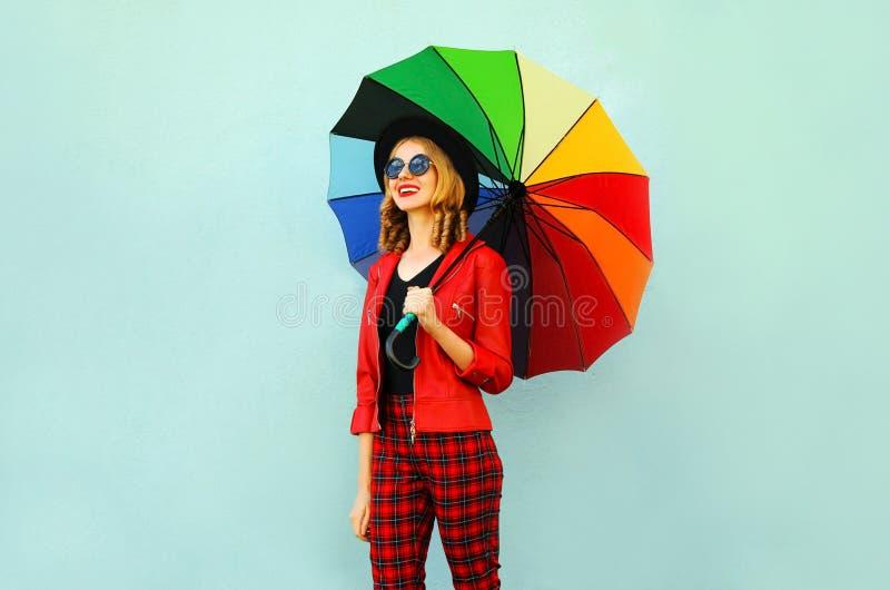 愉快的微笑的年轻女人在手上的拿着五颜六色的伞,佩带的红色夹克,黑帽会议,走在蓝色墙壁上 免版税库存照片