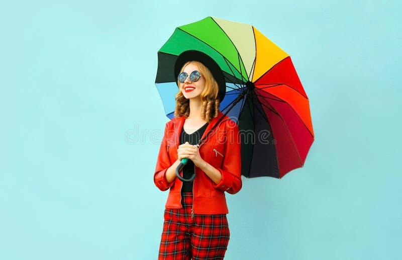 愉快的微笑的年轻女人在手上的拿着五颜六色的伞,佩带的红色夹克,黑帽会议 图库摄影