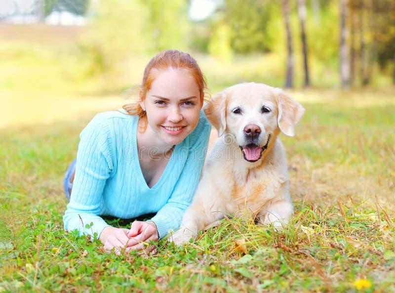 愉快的微笑的所有者妇女和金毛猎犬尾随lyin 免版税库存照片