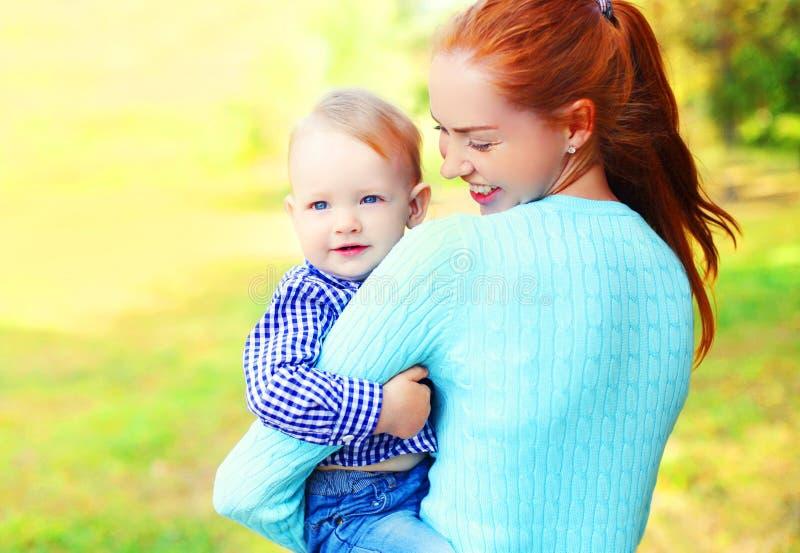 愉快的微笑的母亲和儿子孩子画象户外在晴朗的公园 库存图片