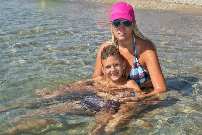 愉快的微笑的母亲和儿子画象海上,室外 库存图片
