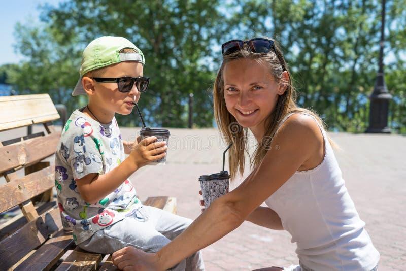 愉快的微笑的母亲和儿童男孩-享受在街道咖啡馆,餐馆,家庭时间,午餐的膳食时间在室外餐馆 Su 免版税库存图片