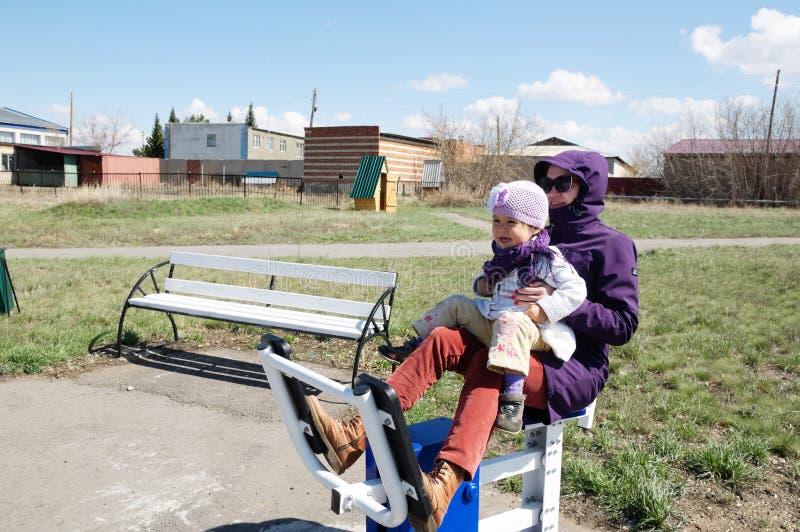 愉快的微笑的母亲和小女孩室外锻炼一起在教练员外面在早期的春天自然公园 体育,母道 免版税库存照片