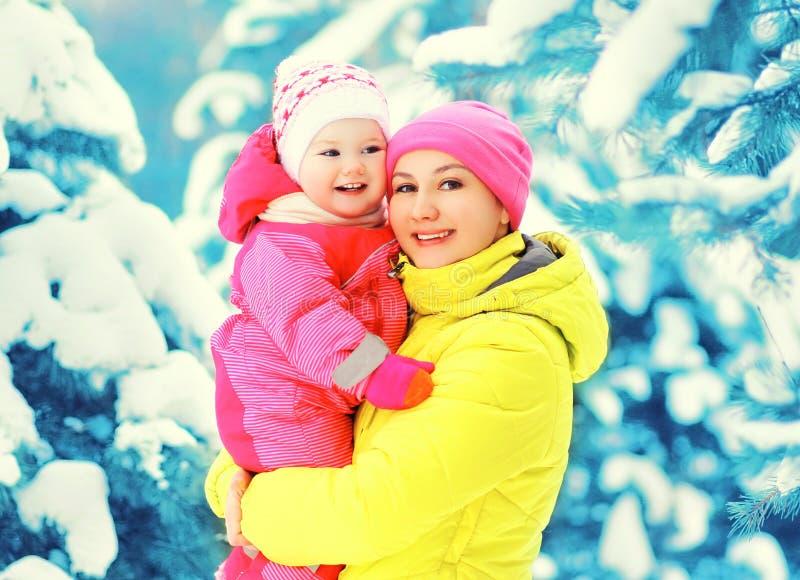 愉快的微笑的母亲抱着婴孩的冬天画象移交多雪的圣诞树 图库摄影
