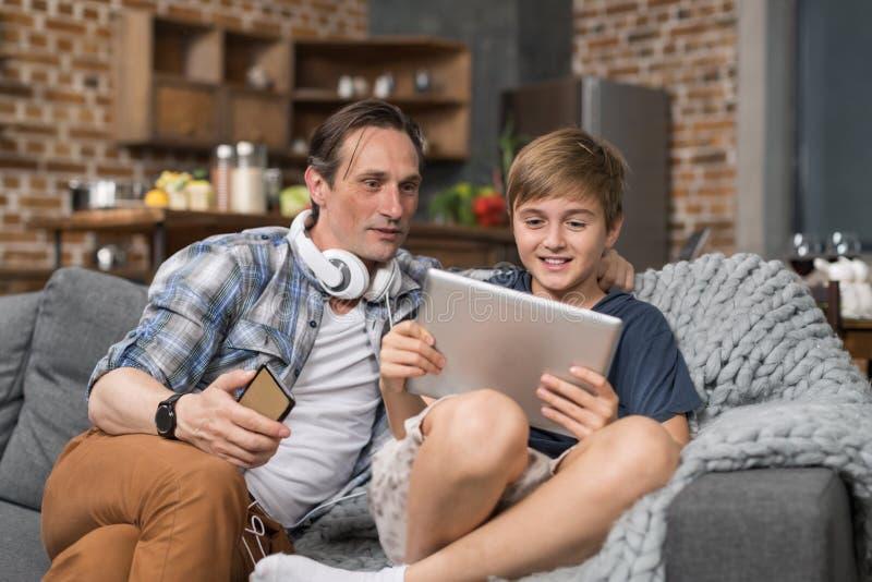 愉快的微笑的父亲和儿子坐长沙发用途片剂计算机,花费时间孩子的父母 库存照片
