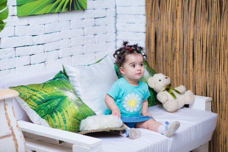 愉快的微笑的甜女婴坐有熊玩具的沙发 免版税库存图片