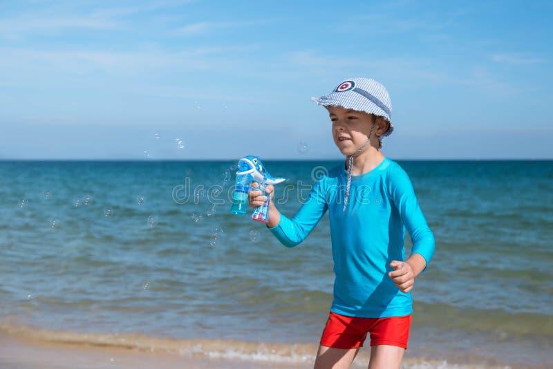 愉快的微笑的男孩蓝色UF防护T恤杉和红色短裤的欧洲人在蓝色海的海滩开始肥皂泡 免版税库存照片