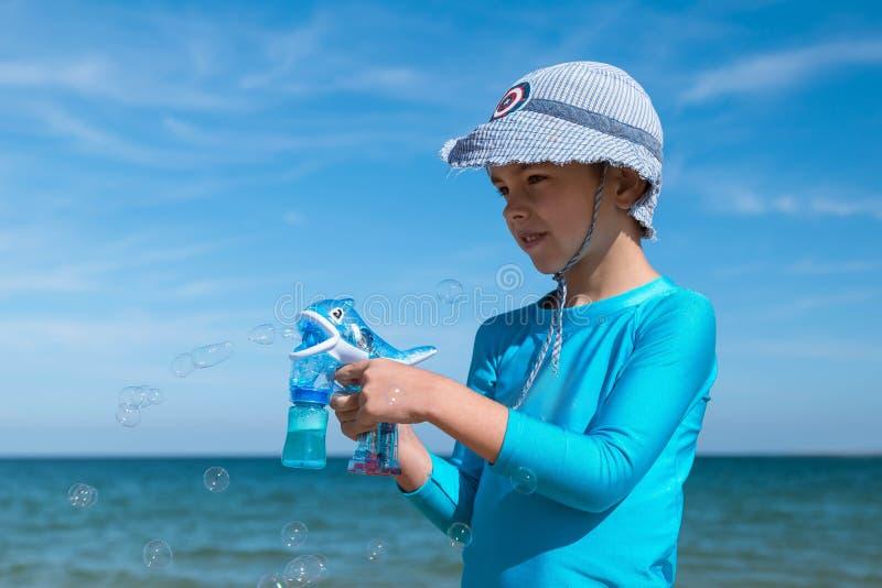 愉快的微笑的男孩蓝色UF防护T恤杉和红色短裤的欧洲人在蓝色海的海滩开始肥皂泡 免版税库存图片