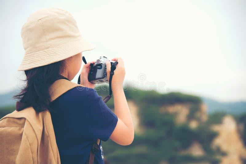愉快的微笑的白种人儿童亚洲女孩背包和举行照相机为在山拍照片登记 免版税图库摄影