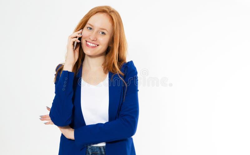 愉快的微笑的红色头发妇女画象谈话在电话,当站立在白色背景时 免版税库存图片