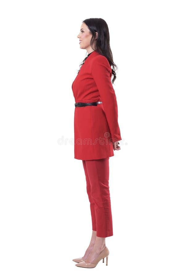 愉快的微笑的美丽的女商人侧视图红色典雅的衣服的用在后面后的手 免版税库存图片