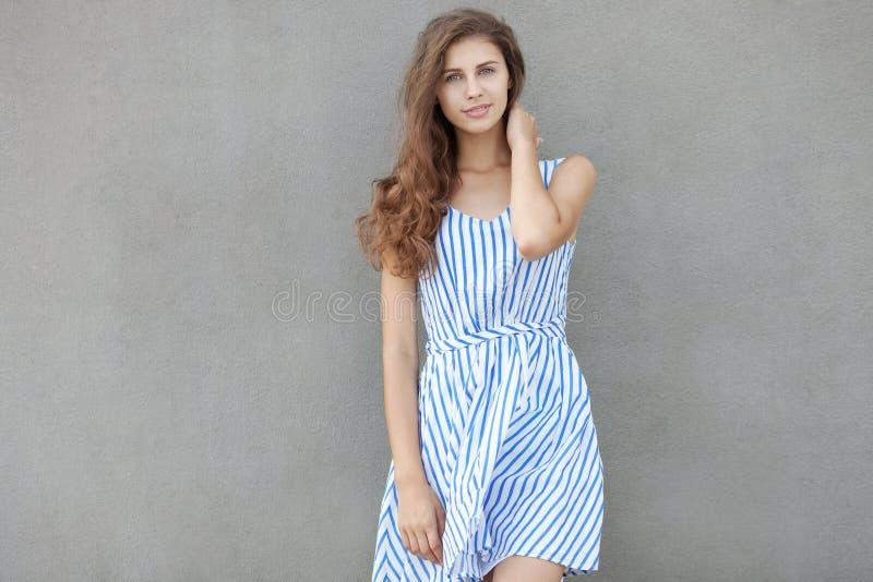 年轻愉快的微笑的美丽的妇女特写镜头画象轻的礼服的有摆在对在温暖的墙壁的长的深色的卷发的 库存照片