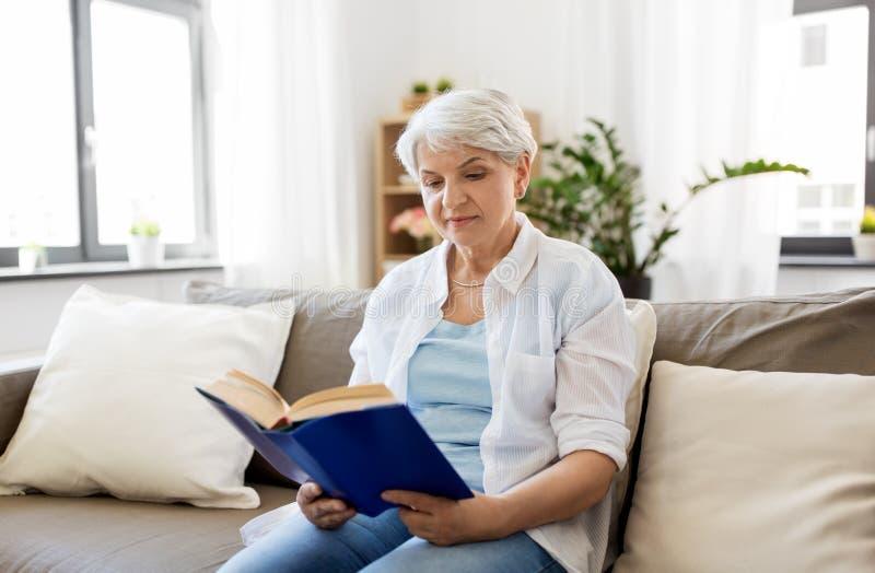 愉快的微笑的资深妇女阅读书在家 免版税库存照片