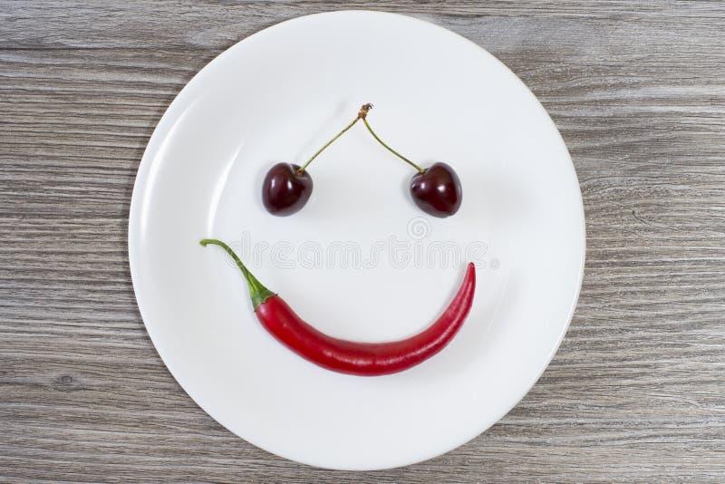 愉快的微笑的面孔由樱桃和辣椒制成在白色板材 顶视图,在头顶上木桌大角度在看法照片上 我们 免版税库存图片