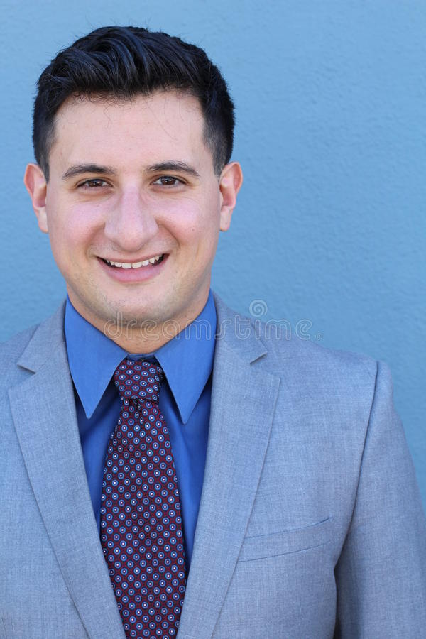 愉快的微笑的年轻反对蓝色背景的商人和领带画象有衣服的 免版税库存图片
