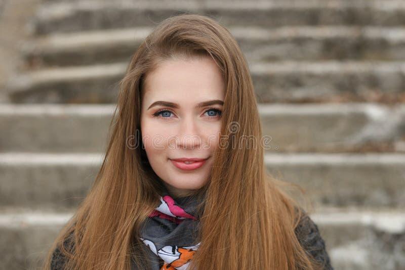 愉快的微笑的年轻和俏丽的妇女生活方式画象有摆在有浅深度的城市公园的华美的长的头发的  图库摄影