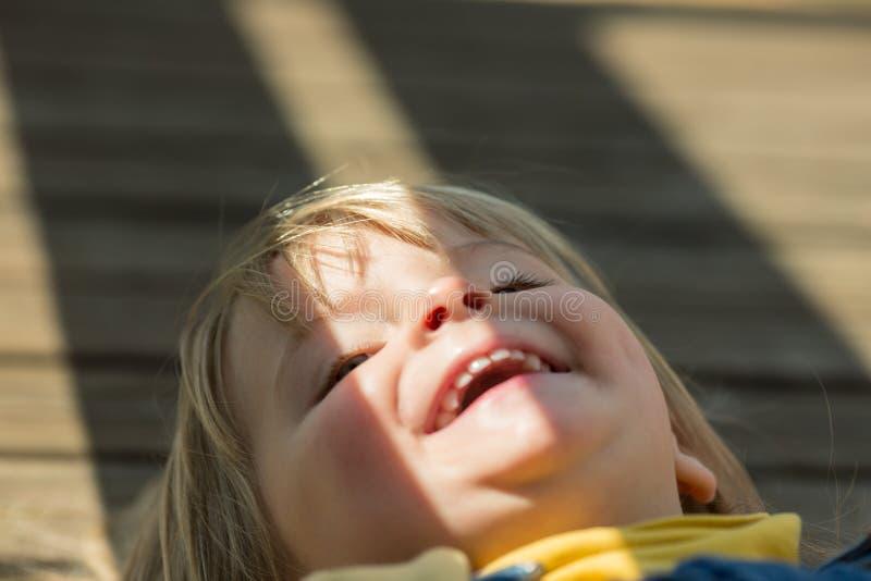 愉快的微笑的年轻婴孩白种人白肤金发的真正的人女孩关闭室外画象 免版税库存图片