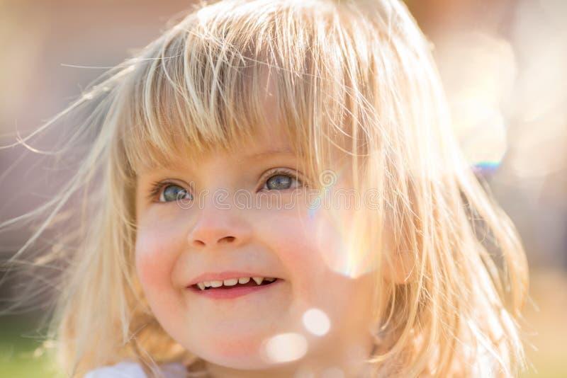 愉快的微笑的年轻婴孩白种人白肤金发的真正的人女孩关闭室外画象 库存图片