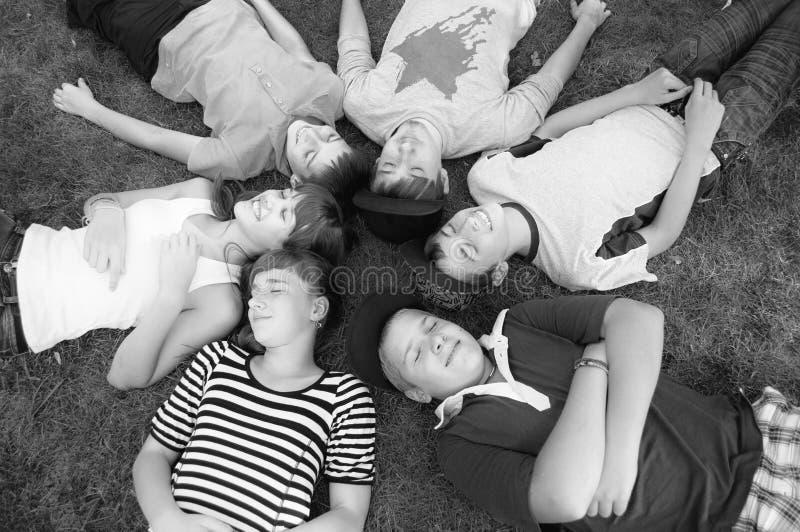 愉快的微笑的说谎在春天草的十几岁的男孩和女孩 免版税图库摄影