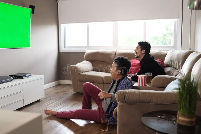 愉快的快乐在电视的夫妇观看的体育比赛在家 免版税库存照片
