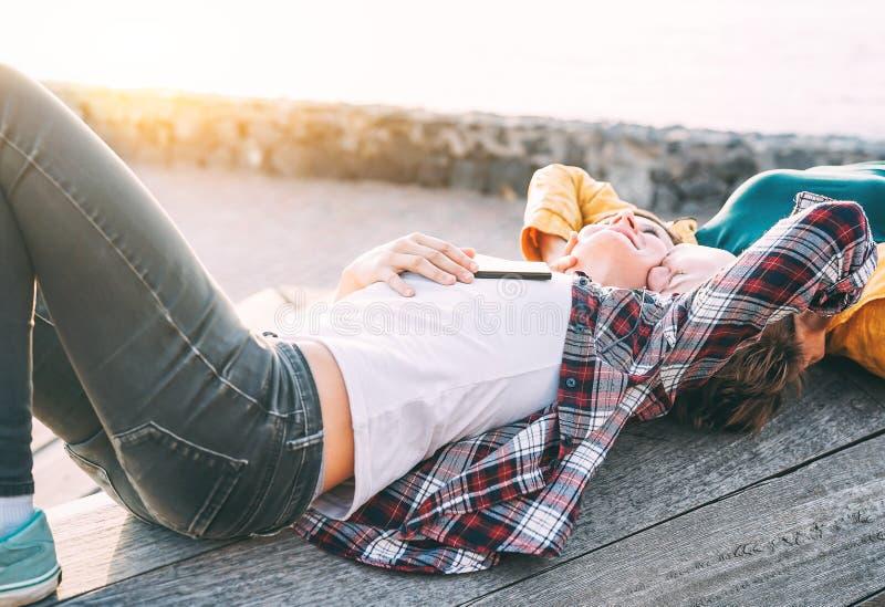 愉快的快乐夫妇说谎在海滩旁边的在日落-有女同性恋的妇女室外嫩浪漫的片刻 库存图片