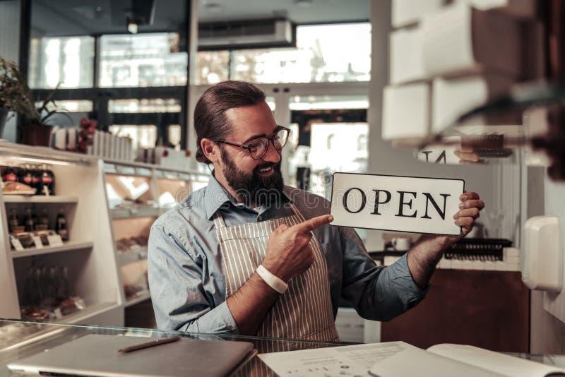 愉快的快乐的人他的咖啡馆为打开做准备 免版税库存照片