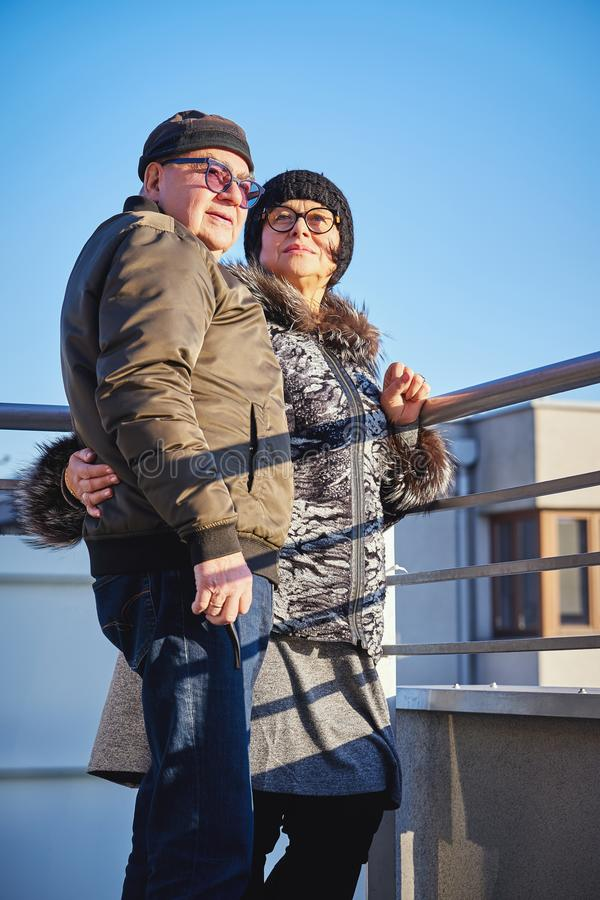 愉快的快乐的前辈夫妇温暖地穿戴了站立在阳台 库存图片