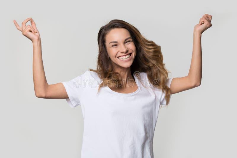 愉快的快乐的在白色背景的年轻女人跳跃的感觉的喜悦 库存图片