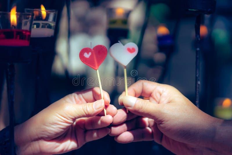 愉快的快乐的夫妇在蜡烛光,爱概念前面互相给心脏蜡烛 库存图片
