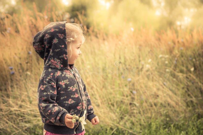 愉快的快乐的孩子女孩微笑的秋天金黄黄色阳光风景概念愉快的无忧无虑的童年生活方式 免版税库存照片