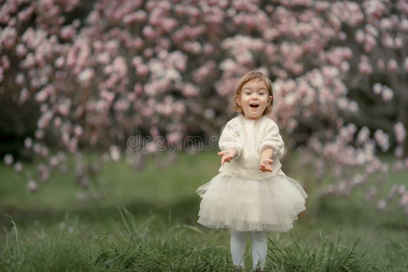 愉快的快乐的孩子画象白色衣裳的在树花开花背景 一起使用的家庭外面 库存照片