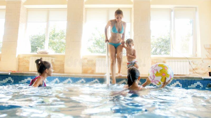 愉快的快乐的家庭照片获得乐趣在游泳场 有三个孩子的年轻母亲与游泳场的健身房的 免版税库存图片