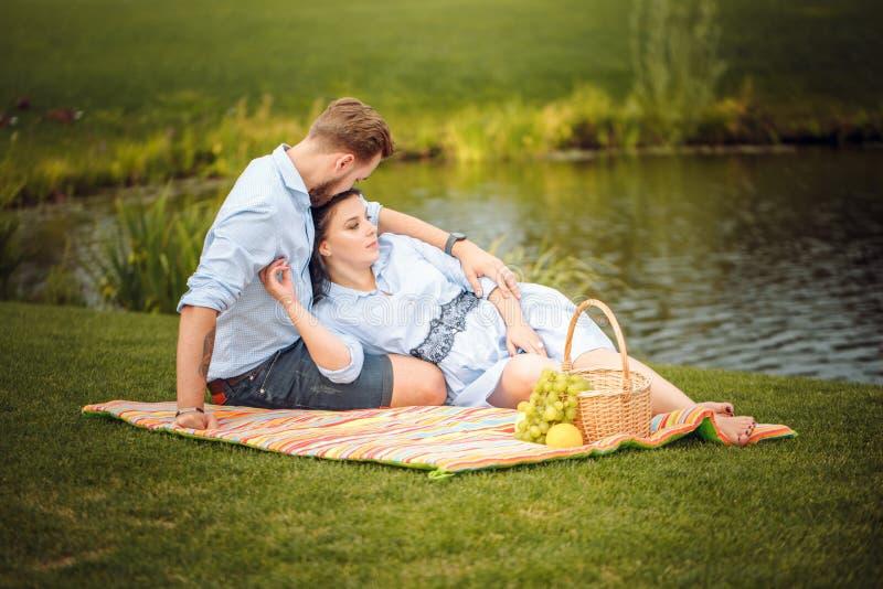 愉快的快乐的年轻家庭丈夫和他怀孕的妻子获得乐趣一起户外,在野餐在夏天公园 库存照片