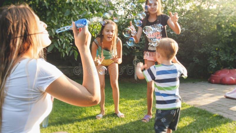 愉快的快乐的年轻家庭吹的和cathcing的肥皂泡滑稽的画象在房子后院庭院的 免版税库存照片